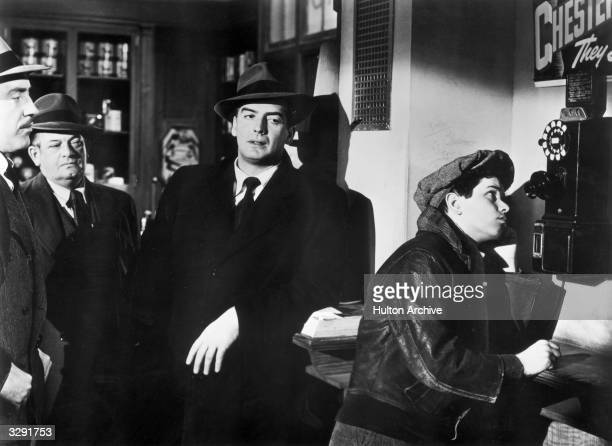 Victor Mature and some of his tough guys watch a boy make a phonecall in the 20th Century Fox filmnoir 'Cry Of The City' a thriller set in New York...
