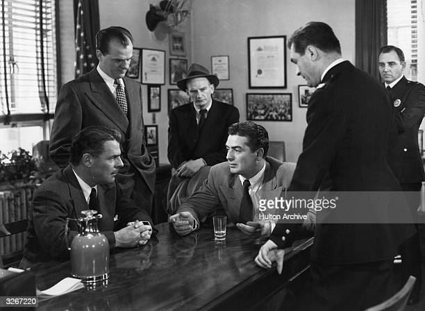 Victor Mature informs on his own criminal gang in a scene from the thriller 'Kiss Of Death' directed by Henry Hathaway for 20th Century Fox
