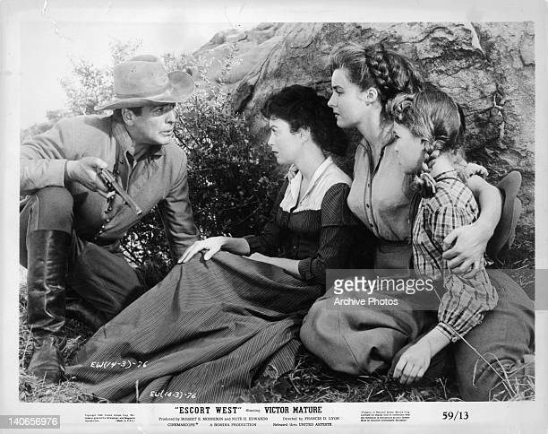 Victor Mature talking to a hiding Faith Domergue Elaine Stewart and child in a scene from the film 'Escort West' 1958
