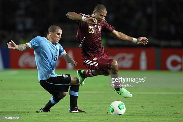 Victor Maximiliano Pereira of Uruguay competes for the ball with Jose Salomon Rondon of Venezuela during a match between Venezuela and Uruguay as...