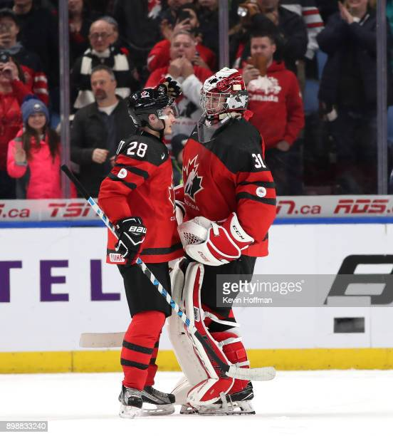Victor Mete of Canada congratulates Carter Hart after winning the game against Finland at KeyBank Center on December 26 2017 in Buffalo New York...