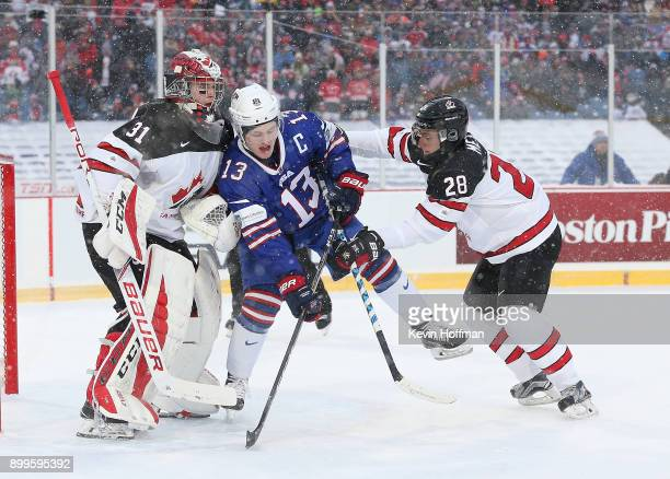 Victor Mete of Canada pushes Joey Anderson of United States into Carter Hart in the first period during the IIHF World Junior Championship at New Era...