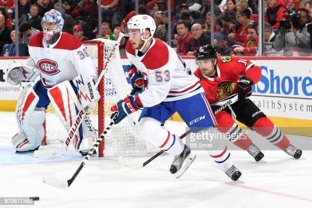 Victor Mete of the Montreal Canadiens approaches the puck next to goalie Charlie Lindgren as Patrick Sharp of the Chicago Blackhawks follows in the...