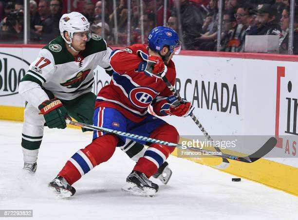 Victor Mete of the Montreal Canadiens skates for the puck against Marcus Foligno of the Minnesota Wild in the NHL game at the Bell Centre on November...