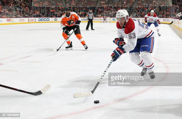 Victor Mete of the Montreal Canadiens skates the puck against Wayne Simmonds of the Philadelphia Flyers on February 8 2018 at the Wells Fargo Center...