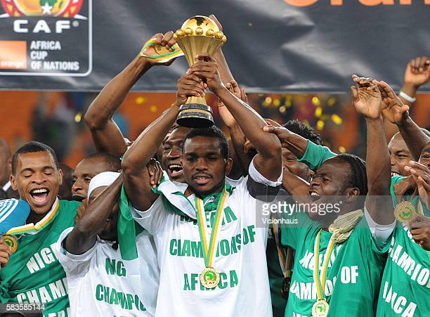 Victor Moses celebrates as Joseph Yobo of Nigeria lifts the trophy after his team win the 2013 African Cup of Nations Final match between Nigeria and...