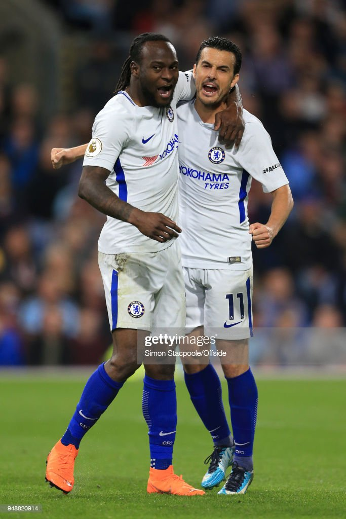 Victor Moses of Chelsea (L) celebrates with teammate Pedro of Chelsea after scoring their 2nd goal during the Premier League match between Burnley and Chelsea at Turf Moor on April 19, 2018 in Burnley, England.