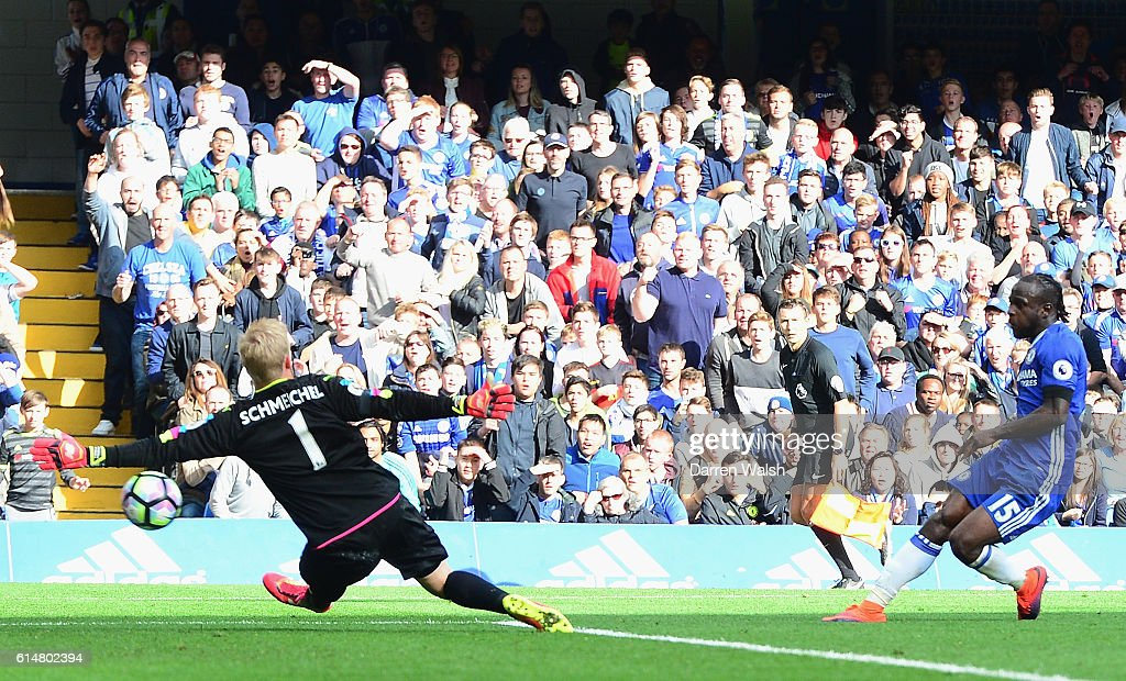 Victor Moses of Chelsea (R) scores his sides third goal past Kasper Schmeichel of Leicester City (L) during the Premier League match between Chelsea and Leicester City at Stamford Bridge on October 15, 2016 in London, England.