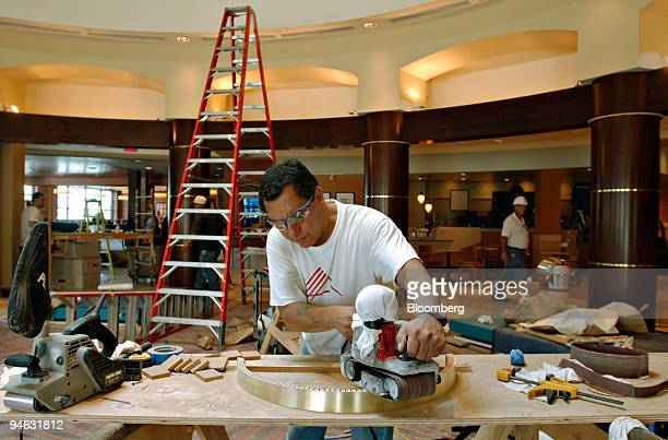 Victor Ochoa of Powell cabinets and fixtures based in Reno Nevada sands a decrative band prior to its installation on a column in the lobby of the...