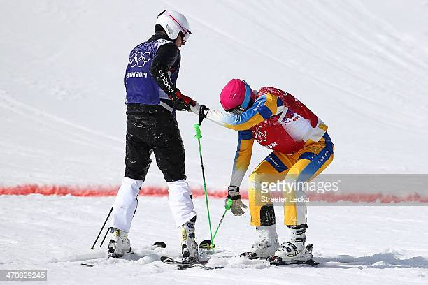 Victor Oehling Norberg of Sweden is helped by Jouni Pellinen of Finland during the Freestyle Skiing Men's Ski Cross Quarter Finals on day 13 of the...