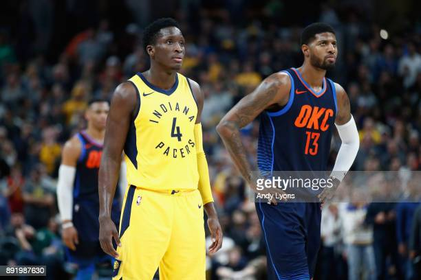 Victor Oladipo of Indiana Pacers and Paul George of the Oklahoma City Thunder watch the action during the game at Bankers Life Fieldhouse on December...