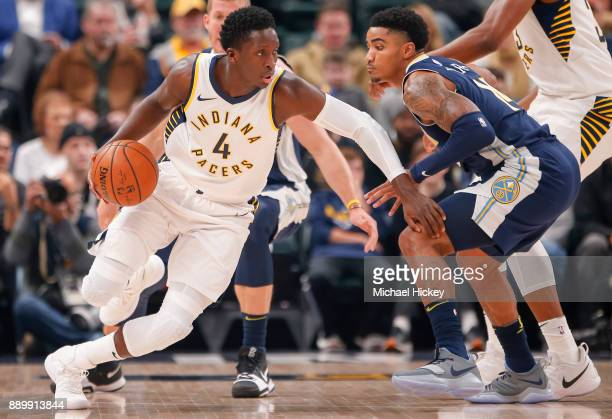 Victor Oladipo of the Indiana Pacers dribbles the ball against Gary Harris of the Denver Nuggets at Bankers Life Fieldhouse on December 10 2017 in...