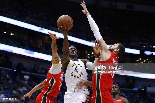 Victor Oladipo of the Indiana Pacers shoots against Nikola Mirotic of the New Orleans Pelicans and Anthony Davis during the second half at the...