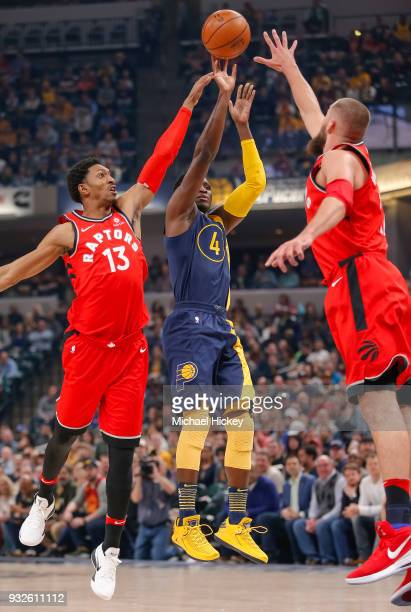 Victor Oladipo of the Indiana Pacers shoots the ball against Jonas Valanciunas and Malcolm Miller of the Toronto Raptors at Bankers Life Fieldhouse...