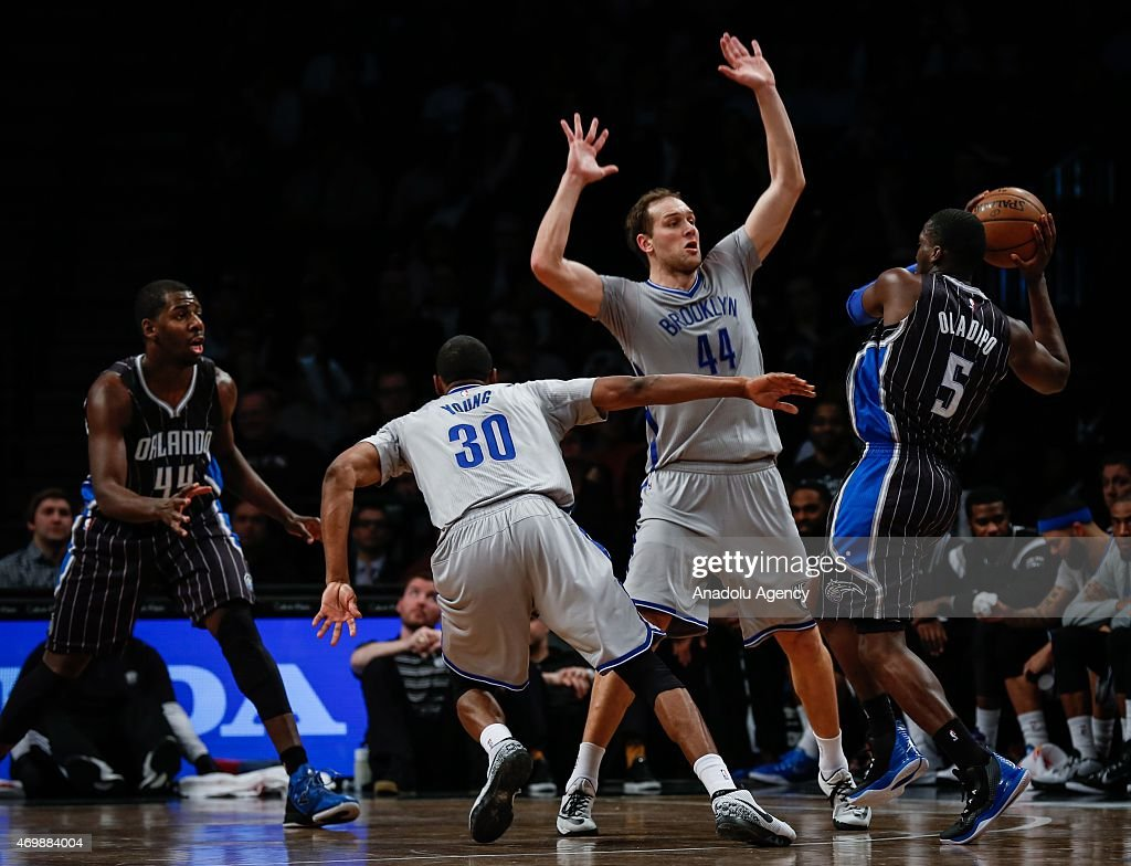 Victor Oladipo (5) of the Orlando Magic in action against Bojan Bogdanovic (2nd R) and Thaddeus Young (30) of the Brooklyn Nets during an NBA basketball game at the Barclays Center in the Brooklyn borough of New York City on April 15, 2015.