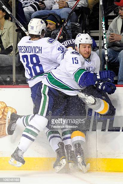 Victor Oreskovich and Tanner Glass of the Vancouver Canucks both check Ryan Suter of the Nashville Predators on February 17 2011 at the Bridgestone...