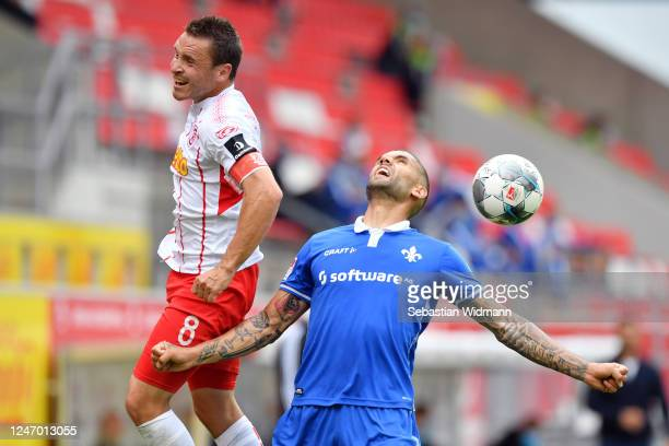 Victor Palsson of Darmstadt is challenged by Andreas Geipl of Regensburg during the Second Bundesliga match between SSV Jahn Regensburg and SV...