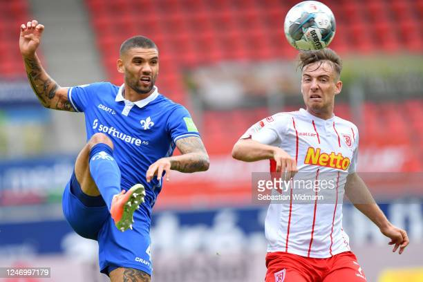 Victor Palsson of Darmstadt is challenged by Max Besuschkow of Regensburg during the Second Bundesliga match between SSV Jahn Regensburg and SV...