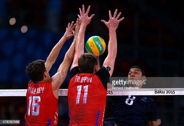 Victor Poletaev and Igor Filippov of Russia and Jhon Wendt of France jump at the net during the Men's Volleyball quarter final match between France...