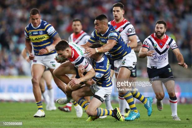 Victor Radley of the Roosters is tackled during the round 25 NRL match between the Parramatta Eels and the Sydney Roosters at ANZ Stadium on...