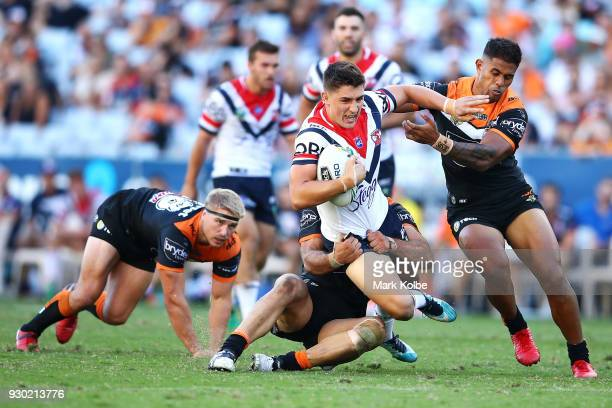 Victor Radley of the Roosters is tackled during the round one NRL match between the Wests Tigers and the Sydney Roosters at ANZ Stadium on March 10...