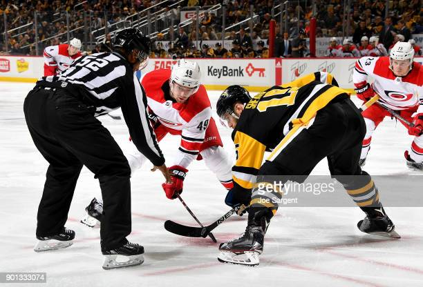 Victor Rask of the Carolina Hurricanes and Riley Sheahan of the Pittsburgh Penguins take a faceoff at PPG Paints Arena on January 4 2018 in...