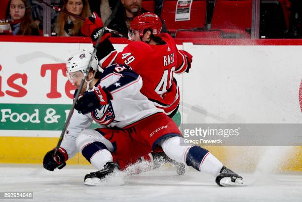 Victor Rask of the Carolina Hurricanes and Tyler Motte of the Columbus Blue Jackets battle along the boards to control the puck during an NHL game on...