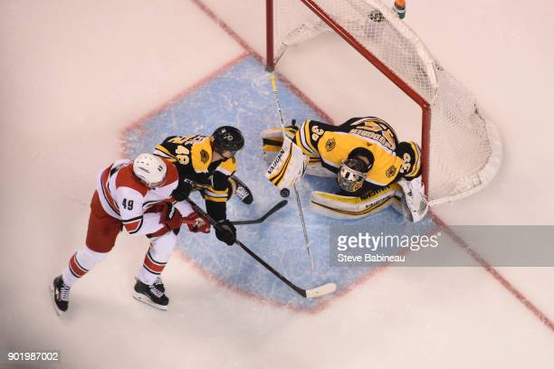 Victor Rask of the Carolina Hurricanes fights for the puck against Matt Grzelcyk and Tuukka Rask of the Boston Bruins at the TD Garden on January 6...