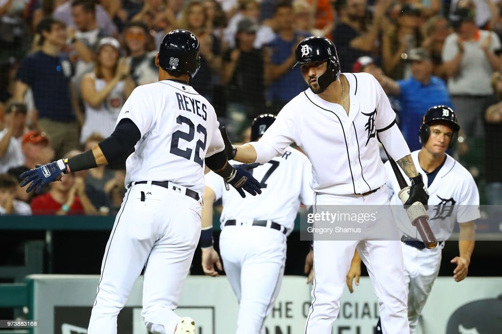 Victor Reyes #22 of the Detroit Tigers celebrates scoring a eighth inning run with Nicholas Castellanos #9 while playing the Minnesota Twins at Comerica Park on June 13, 2018 in Detroit, Michigan.