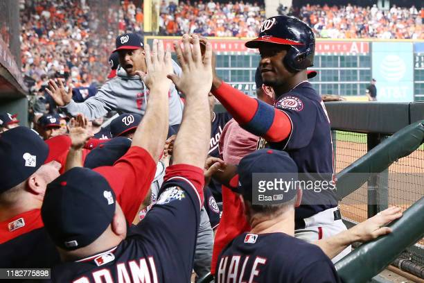 Victor Robles of the Washington Nationals is congratulated by his teammates after scoring a run on a double by Juan Soto against the Houston Astros...