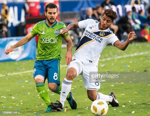 Victor Rodriguez of Seattle Sounders battles Jonathan dos Santos of Los Angeles Galaxy during the Los Angeles Galaxy's MLS match against Seattle...