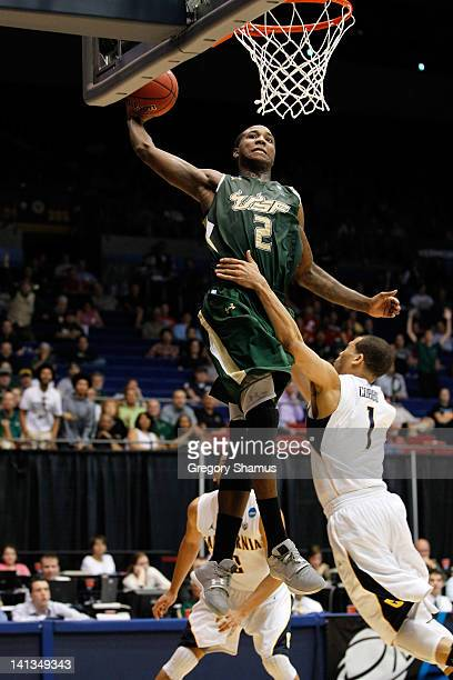 Victor Rudd Jr #2 of the South Florida Bulls dunks in the second half against Justin Cobbs of the California Golden Bears in the first round of the...