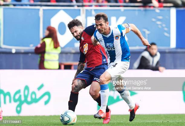 Victor Sanchez of RCD Espanyol duels for the ball with Ruben Garcia of CA Osasuna during the Liga match between CA Osasuna and RCD Espanyol at El...