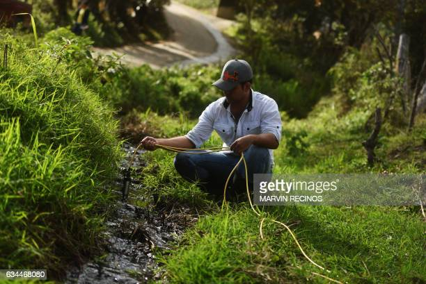 Victor Sandoval an environmental monitoring technician form the University of San Carlos of Guatemala collects water samples for analysis near the...