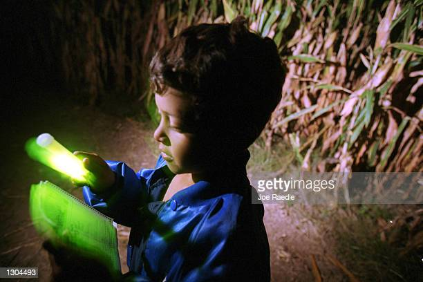 Victor Segura uses a glow stick to check his map as he trys to find his way out of the 10 acre cornfield maze October 19 2000 in La Union NM The...