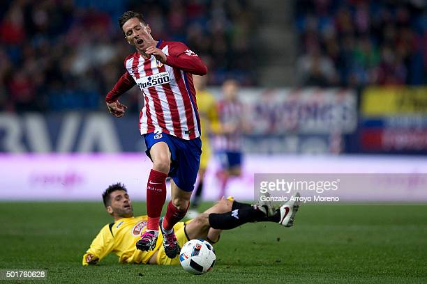 Victor Silva of CF Reus tackles Fernando Torres of Atletico de Madrid during the Copa del Rey Round of 32 match between Club Atletico Madrid and CF...