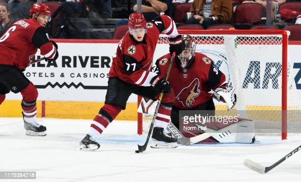 Victor Soderstrom of the Arizona Coyotes tries to clear the puck away from goalie Antti Raanta of the Coyotes during the first period of an NHL...