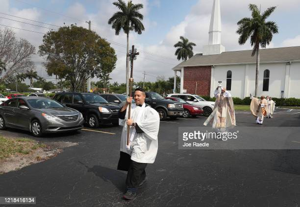 Victor Tito Ramos carries the cross as he takes part in an Easter service procession through the parking lot of the Sunshine Cathedral on April 12...