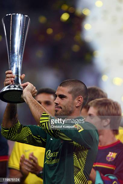 Victor Valdés of Barcelona lifst the Audi trophy after winning 20 the Audi Cup final match between FC Bayern Muenchen and FC Barcelona at Allianz...