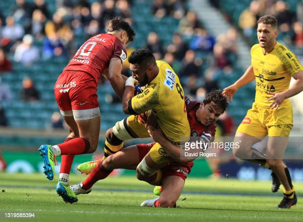Victor Vito of La Rochelle is tackled by Antoine Dupont and Romain Ntamack during the Heineken Champions Cup Final match between La Rochelle and...