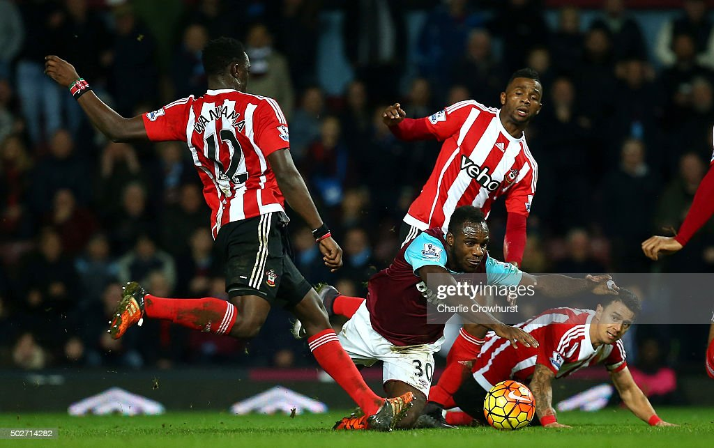 Victor Wanyama of Southampton (L) attempts to clear the ball but is deflected off Michail Antonio of West Ham United (c) for his side's first goal during the Barclays Premier League match between West Ham United and Southampton at the Boleyn Ground on December 28, 2015 in London, England.