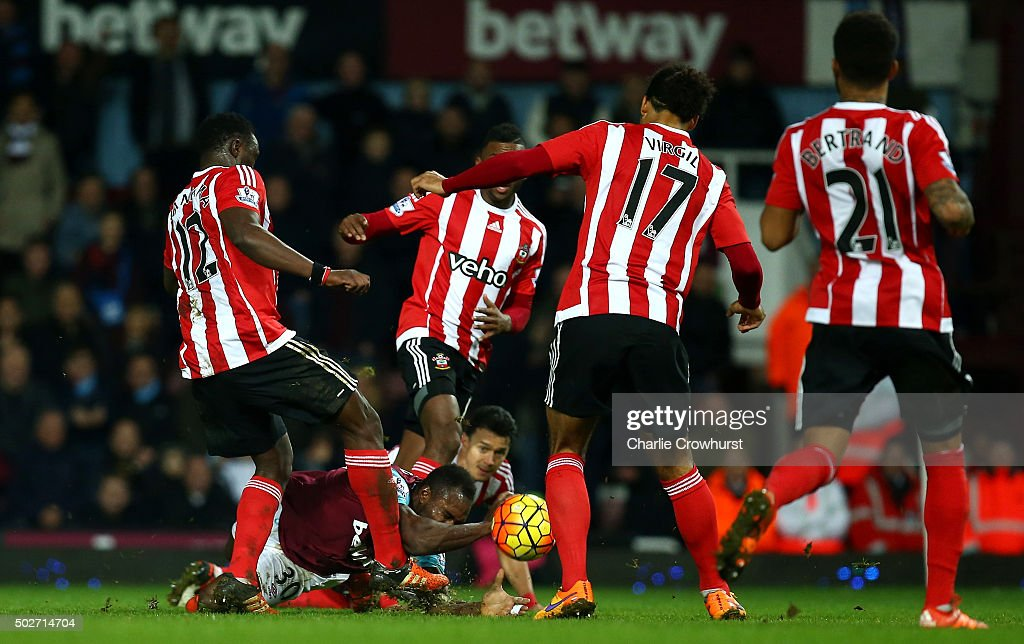 Victor Wanyama of Southampton (L) attempts to clear the ball but is deflected off Michail Antonio of West Ham United (2L) for his side's first goal during the Barclays Premier League match between West Ham United and Southampton at the Boleyn Ground on December 28, 2015 in London, England.