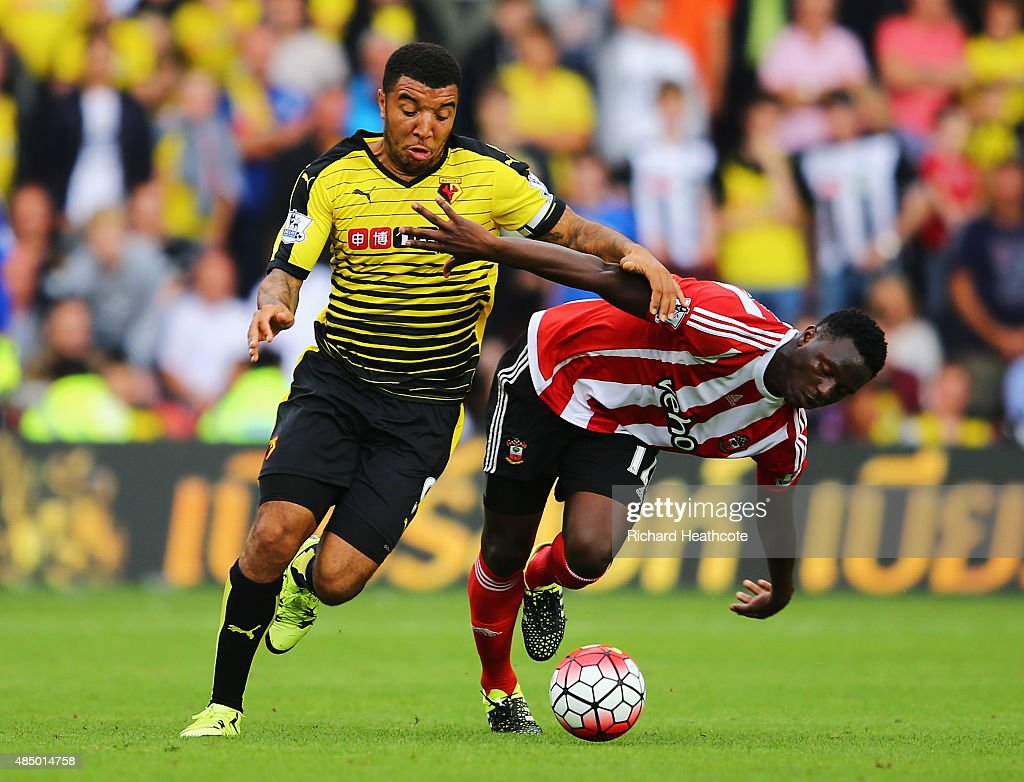 Victor Wanyama of Southampton is challenged by Troy Deeney of Watford during the Barclays Premier League match between Watford and Southampton at Vicarage Road on August 23, 2015 in Watford, England.