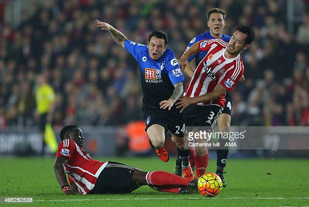 Victor Wanyama of Southampton tackles Lee Tomlin of Bournemouth and is subsequently shown a red card and sent off as Maya Yoshida of Southampton also...
