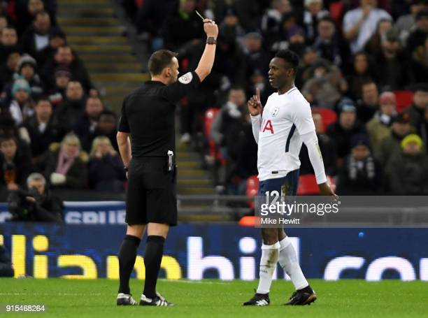 Victor Wanyama of Tottenham Hotspur is shown a yellow card by referee Stuart Attwell during The Emirates FA Cup Fourth Round Replay match between...