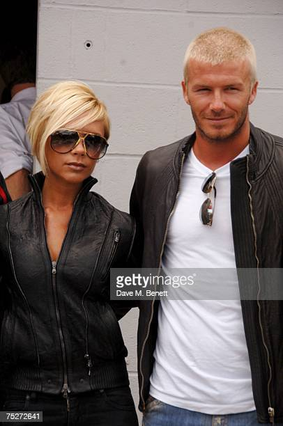 Victoria and David Beckham pose with racing driver Rubens Barrichello at the F1 Grand Prix of Great Britain at Silverstone on July 8 2007 in...