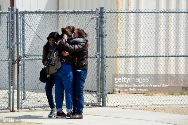 Victoria Aquino hugs her two daughters Melany 17 and Halie as the family was reunited outside Highland High School in Palmdale after Sheriff took the...