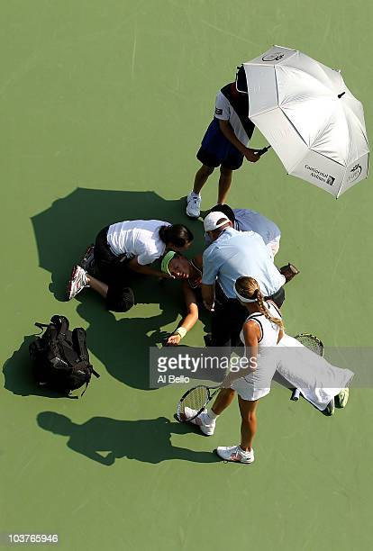 Victoria Azarenka of Belarus is tended to by medical personnel on the court after she collapsed during her second round women's singles match against...
