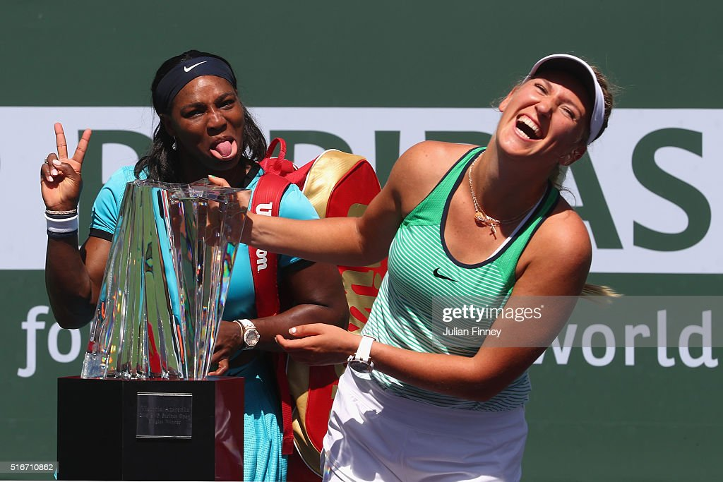Victoria Azarenka of Belarus laughs with the winners trophy as Serena Williams of USA pulls a face after the final during day fourteen of the BNP Paribas Open at Indian Wells Tennis Garden on March 20, 2016 in Indian Wells, California.