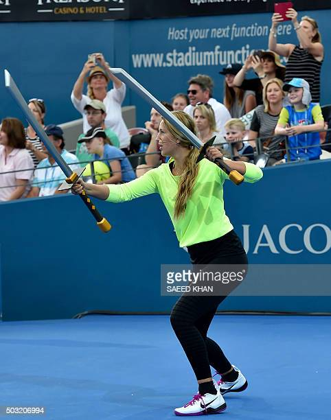 Victoria Azarenka of Belarus plays with big toy ninjastyle swords during an event ahead of the start of the Brisbane International tennis tournament...